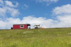 Silueta del tractor con el remolque de casa contra un cielo azul Foto de archivo libre de regalías