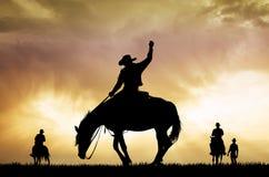Silueta del vaquero del rodeo en la puesta del sol Fotografía de archivo libre de regalías