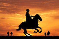 Silueta del vaquero del rodeo en la puesta del sol Foto de archivo