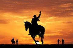 Silueta del vaquero del rodeo en la puesta del sol Fotos de archivo