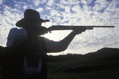 Silueta del vaquero que apunta el rifle Foto de archivo libre de regalías