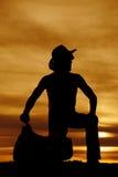 Silueta del vaquero que se arrodilla por mirada de la silla de montar al lado Imagenes de archivo