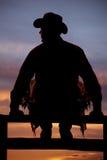 Silueta del vaquero que se sienta en la cerca Foto de archivo libre de regalías