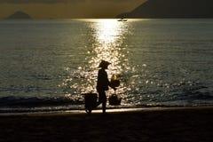 Silueta del vendedor de la comida contra la reflexión del haz del sol en la playa en el amanecer fotos de archivo