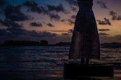 Silueta del vestido en la puesta del sol, fondo ocan hermoso imagen de archivo