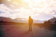 Silueta del viajero masculino con la mochila que camina contra la luz del sol en área de la montaña de la montaña Imagenes de archivo