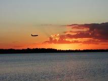 Silueta del vuelo del aeroplano en un cielo de la puesta del sol Imagen de archivo libre de regalías