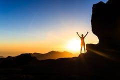 Silueta del éxito del escalador de la mujer en montañas, el océano y la puesta del sol Fotografía de archivo libre de regalías