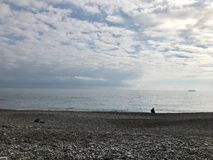 Silueta distante de un turista que se sienta en la playa Imagen de archivo