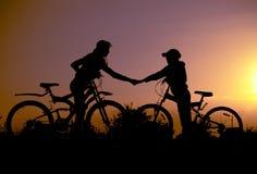 Silueta dos con las bicicletas en la puesta del sol Fotos de archivo