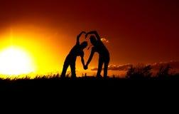 Silueta dos en la puesta del sol, un muchacho y una muchacha, una declaración del amor Imagenes de archivo