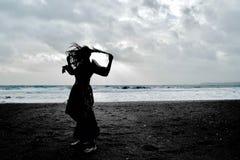 Silueta dramática de una señora de pelo largo en vestido formal floral en una playa tempestuosa fotografía de archivo libre de regalías