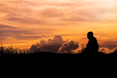 Silueta - el monje budista Meditation y nubes que igualan el cielo fotografía de archivo