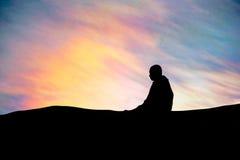 Silueta - el monje budista Meditation y rayos coloridos del ` s del sol en el cielo imagen de archivo