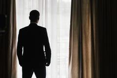 Silueta elegante del novio en el traje que presenta en la luz de la ventana confíe fotografía de archivo libre de regalías