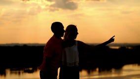 Silueta en amor en puesta del sol La muchacha muestra la distancia almacen de metraje de vídeo