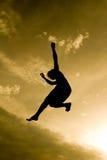 Silueta en cielo en el trampolín Foto de archivo