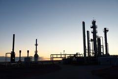 Silueta en el amanecer de tubos y torres en un centro de procesamiento de la industria del petróleo y gas fotos de archivo libres de regalías