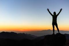 Silueta en montañas, inspi del éxito del escalador de la mujer del logro Foto de archivo libre de regalías
