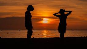 Silueta feliz de la mujer que se opone a puesta del sol con los brazos aumentados Imagenes de archivo