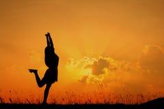 Silueta feliz de la mujer y de la puesta del sol en día relajante Fotografía de archivo libre de regalías
