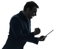 Silueta feliz del éxito de la tableta digital del hombre de negocios Imagenes de archivo