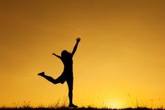 Silueta feliz del salto y de la puesta del sol de la mujer Imagen de archivo libre de regalías