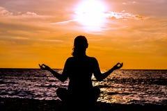 Silueta femenina de los lotos de la yoga en la playa hermosa durante puesta del sol Imagenes de archivo