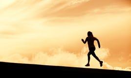 Silueta femenina del corredor, corriendo en puesta del sol Imagen de archivo