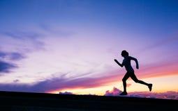 Silueta femenina del corredor, corriendo en puesta del sol Foto de archivo