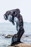 Silueta femenina envuelta en la tela negra que presenta en la playa rocosa Imágenes de archivo libres de regalías
