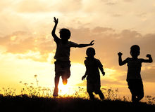 Silueta, grupo de niños felices Imagenes de archivo