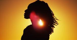 Silueta hermosa de la mujer africana que se coloca en la puesta del sol Fotos de archivo