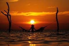 Silueta hermosa de la mujer joven con el oscilación que presenta en el mar en la puesta del sol, paisaje romántico maldivo fotos de archivo