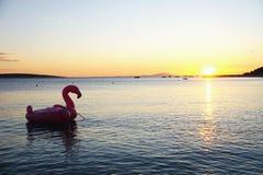 Silueta inflable del flamenco en superficie del mar en la puesta del sol hermosa fotografía de archivo