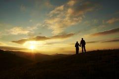 Silueta joven de la familia para la puesta del sol Imagenes de archivo