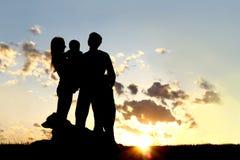 Silueta joven feliz de la familia y del perro en la puesta del sol imagenes de archivo