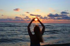 Silueta La muchacha hermosa joven cruzó sus manos bajo la forma de corazón, a través del cual los rayos del sol hacen la manera Imagen de archivo
