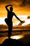 Silueta marcial del artista con puesta del sol anaranjada Imagen de archivo libre de regalías