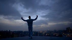 Silueta masculina del ganador y paisaje urbano de la noche en el fondo, alcanzando metas fotos de archivo