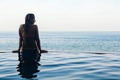 Silueta negra de la mujer en la piscina del infinito Foto de archivo