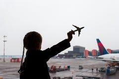 Silueta negra de un pequeño juguete del modelo del aeroplano en aeropuerto en manos de los niños imagenes de archivo