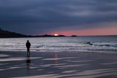 Silueta negra y blanca del hombre que camina solamente en la playa durante el Su imagen de archivo