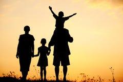 Silueta, niños felices con la madre y padre Fotos de archivo libres de regalías