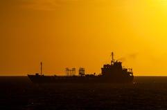 Silueta oscura del barco en la puesta del sol Imágenes de archivo libres de regalías
