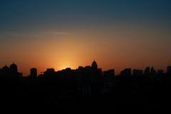 Silueta panorámica de una ciudad grande en la puesta del sol Imagen de archivo
