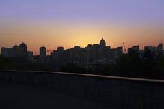 Silueta panorámica de una ciudad grande en la puesta del sol Fotos de archivo libres de regalías