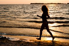 Silueta que brilla intensamente oscura de la mujer que corre a lo largo de la playa imagen de archivo