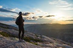 Silueta que camina acertada de la mujer en montañas, la motivación y la inspiración en puesta del sol fotos de archivo