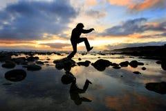 Silueta que salta en la puesta del sol fotos de archivo